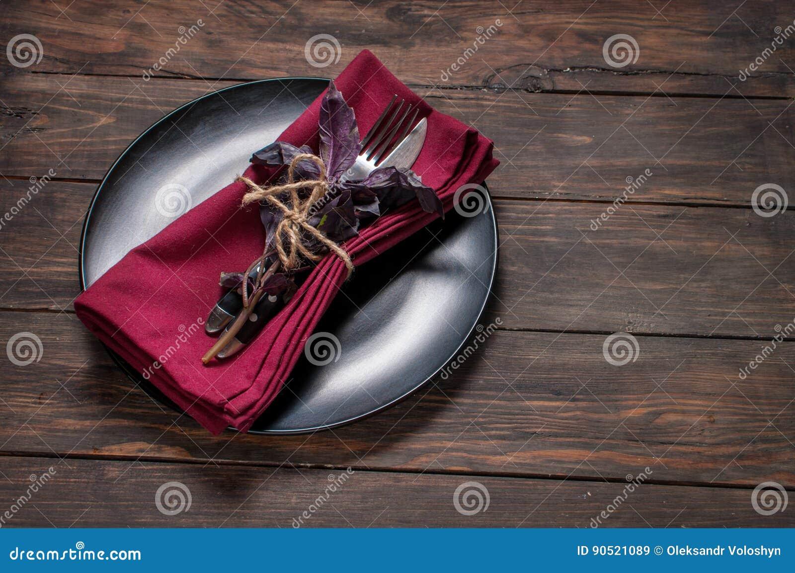 Czarny talerz z rozwidleniem, nożem, pieluchą i basilem na drewnianym stole,