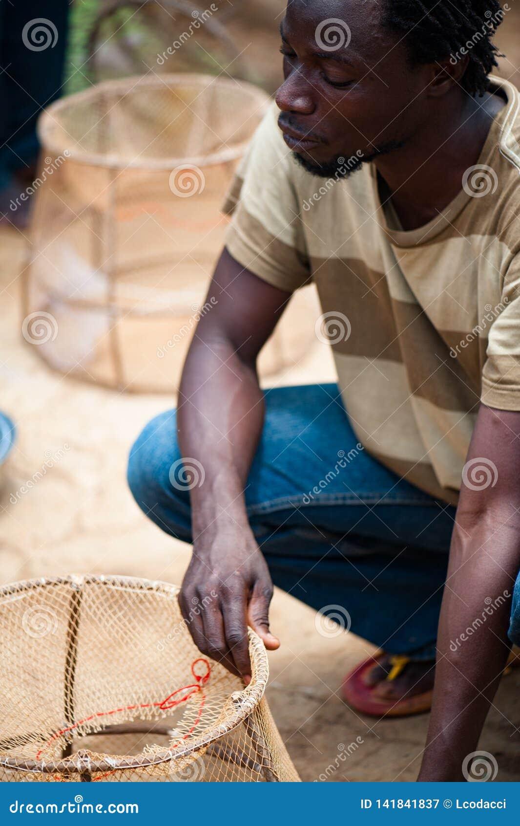 Czarnych Afrykanów ludzie zbiera ryby i przygotowywa