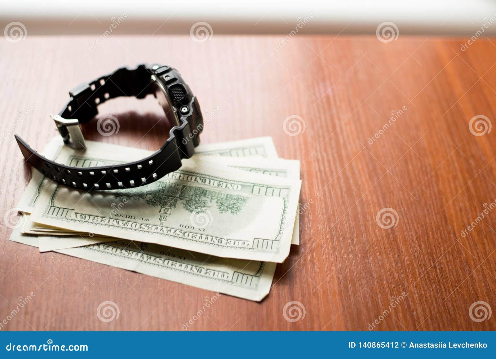Czas jest pieniądze Sto dolarów i czarnego zegarek na drewnianym stole