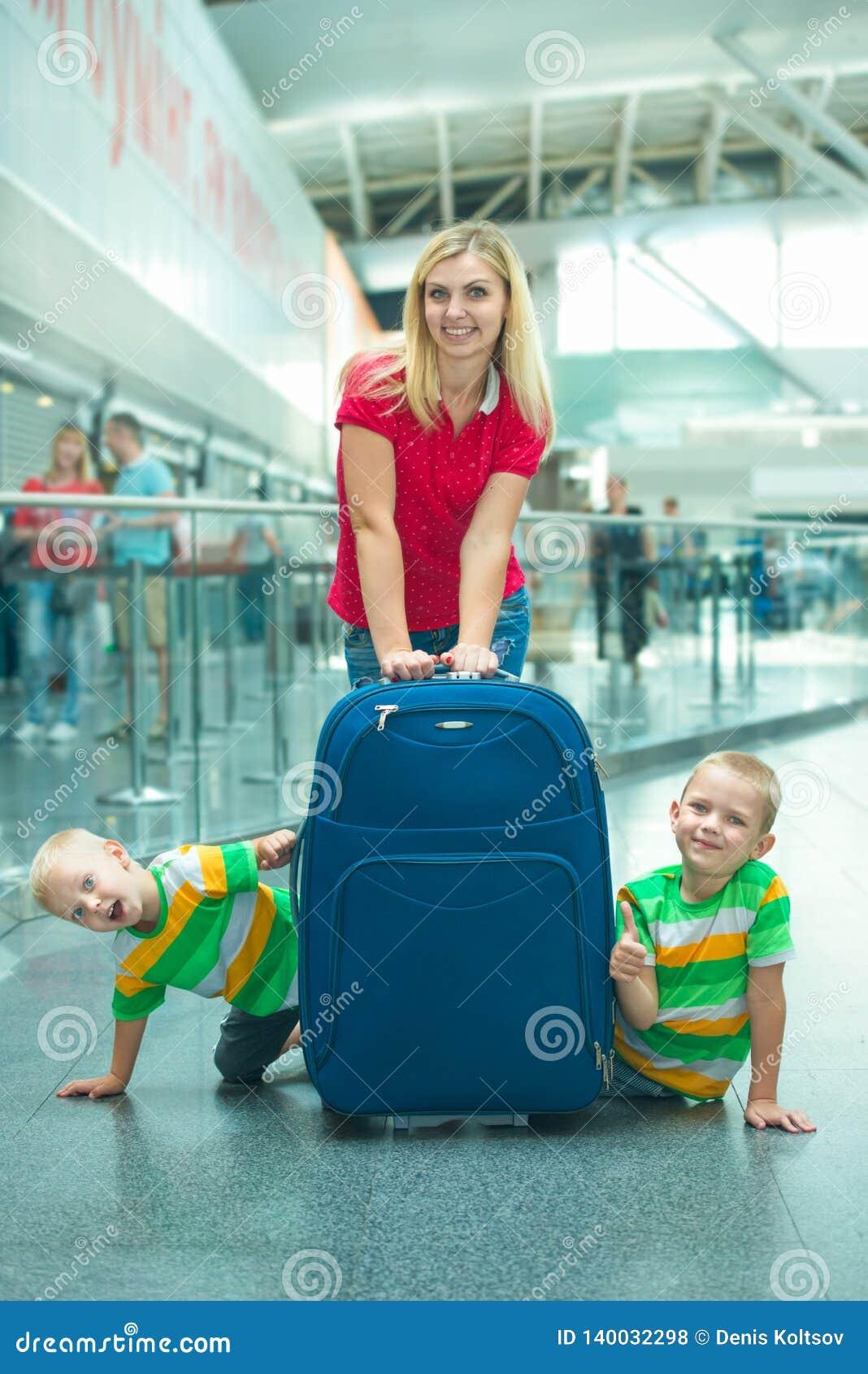 Czas wolny przy lotniskiem Rodzina czekać na swój lot Dwa brata bawić się, chujący za wielką walizką