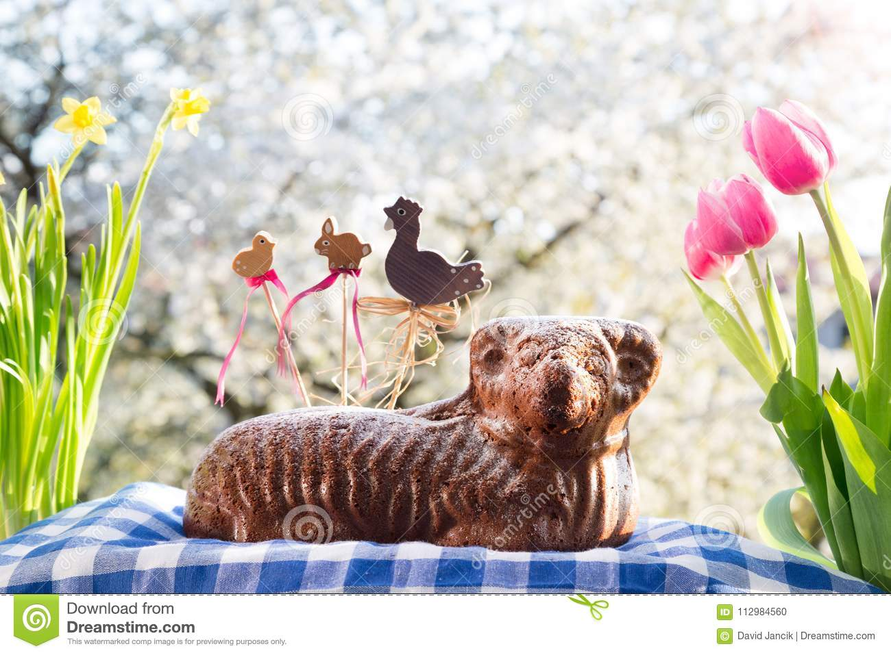 Czech Easter - baked lamb with decorations, flowers and flowering cherry in the background