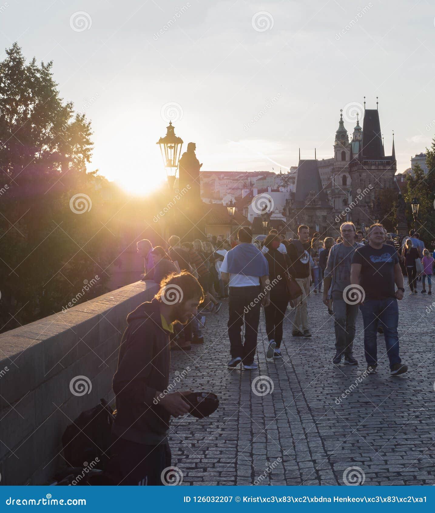 Czech Republic, Prague , September 8, 2018: Young man begging on Charles Bridge on Mala Strana Bridge Tower with walking tourist p