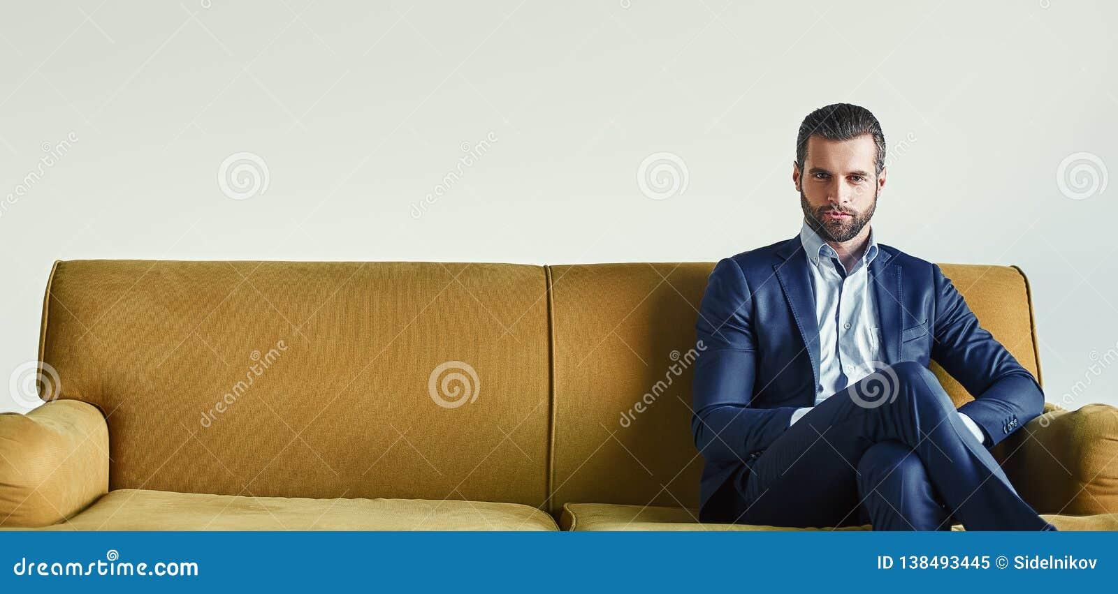 Czekać spotkania Ubierający młody i pomyślny biznesmen siedzi na kanapie przy biurem i czeka somebody