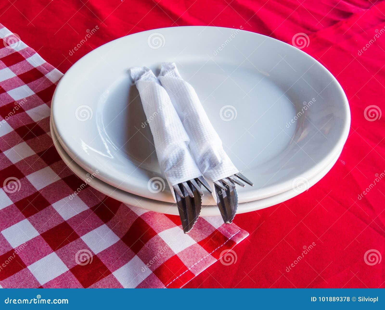 Czekający gościa restauracji, naczynia i cutlery czyścili na czerwonych ręcznikach