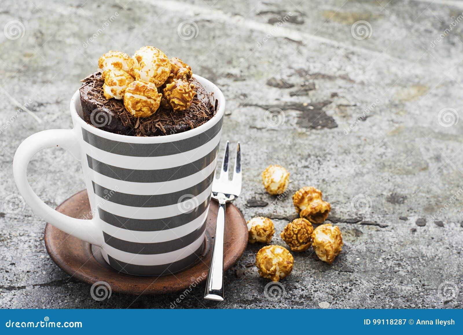 Czekoladowy aromatyczny kubka tort z karmelu apetycznym popkornem dla jesieni wygodnej ciepłej herbaty pije na szarym kamiennym t