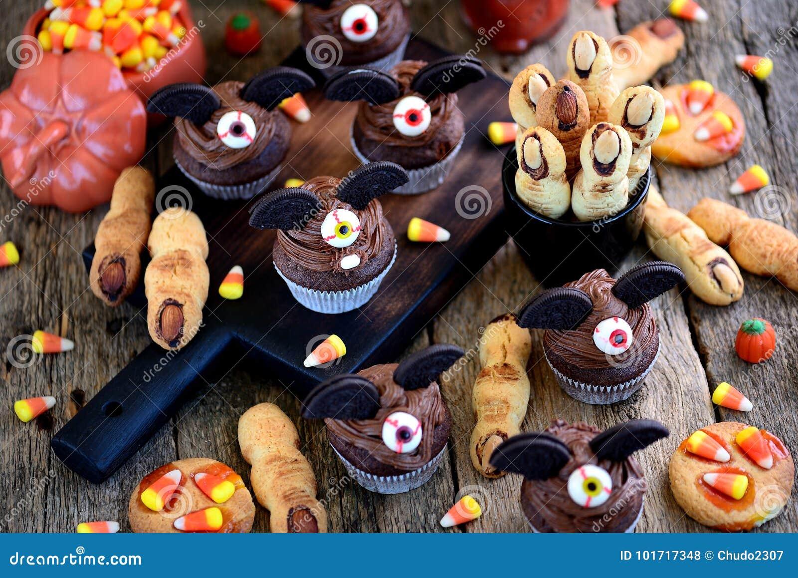 Czekoladowy babeczki ` uderza ` i shortbread ciastek ` czarownicy ` s dotyka ` - wyśmienicie piekarnia cukierki dla świętowania H