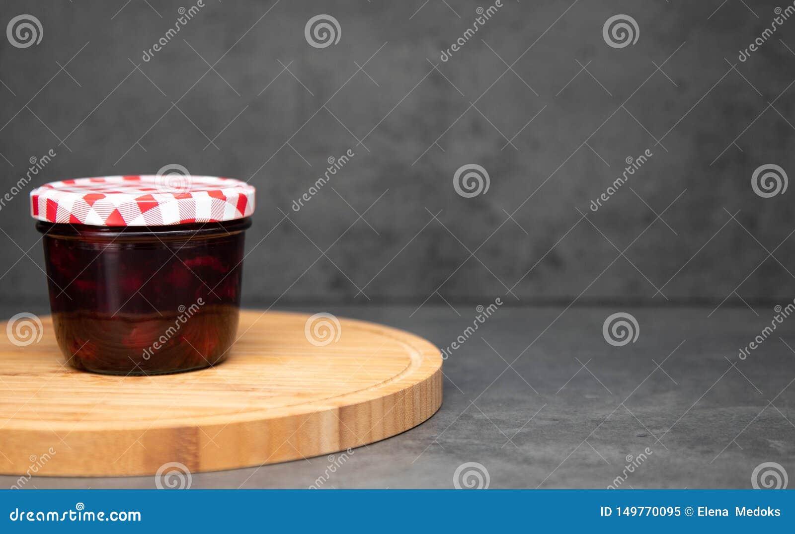 Czereśniowy dżem w szklanym słoju z zamkniętym czerwieni i bielu deklem na drewnianym talerzu Szary t?o Wiśni galareta w słoju na