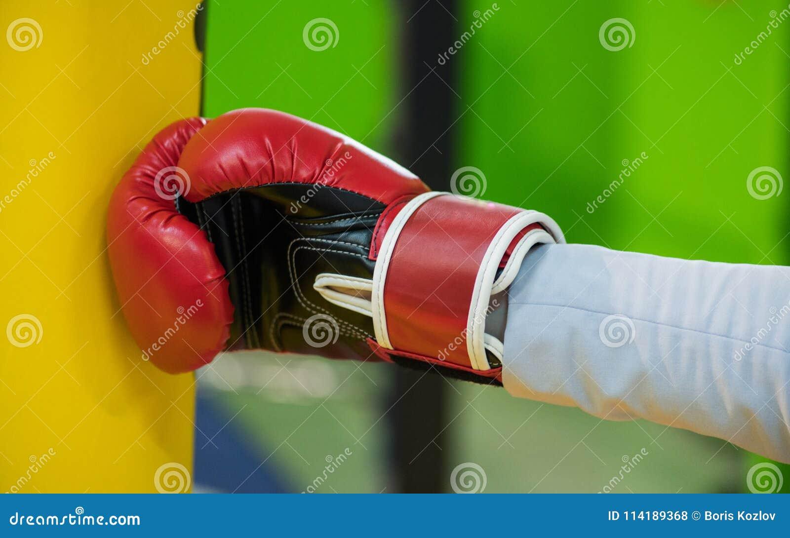 Czerep ręka w Bokserskiej czerwonej rękawiczce uderza żółtej bonkrety, a