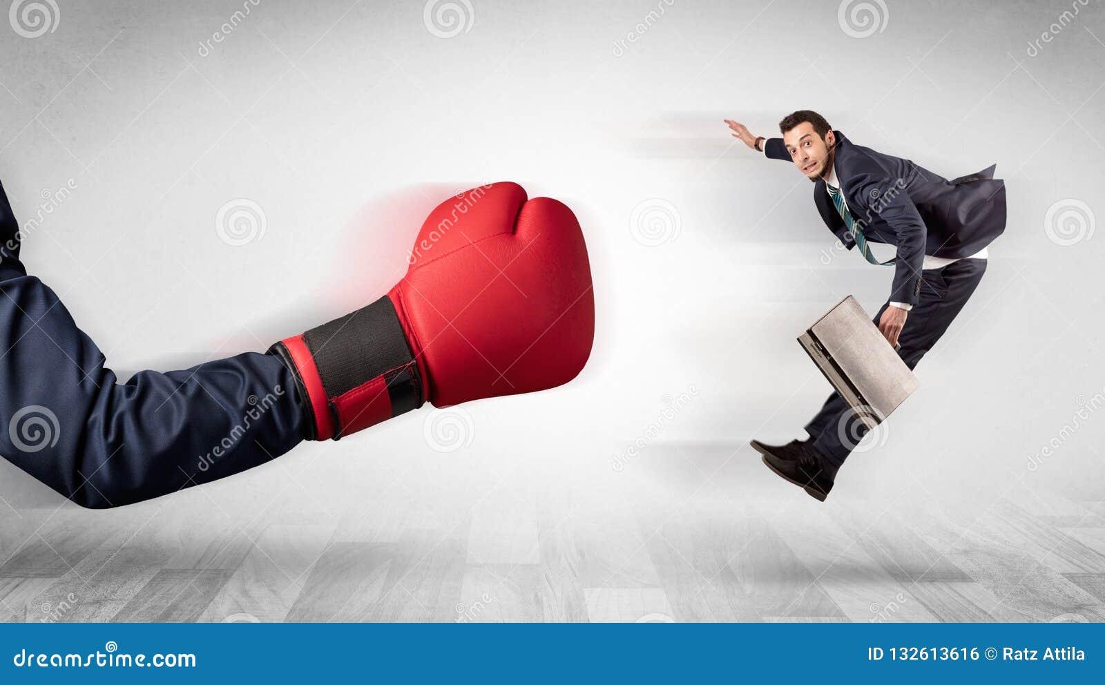 Czerwona bokserska rękawiczka puka out małego biznesmena