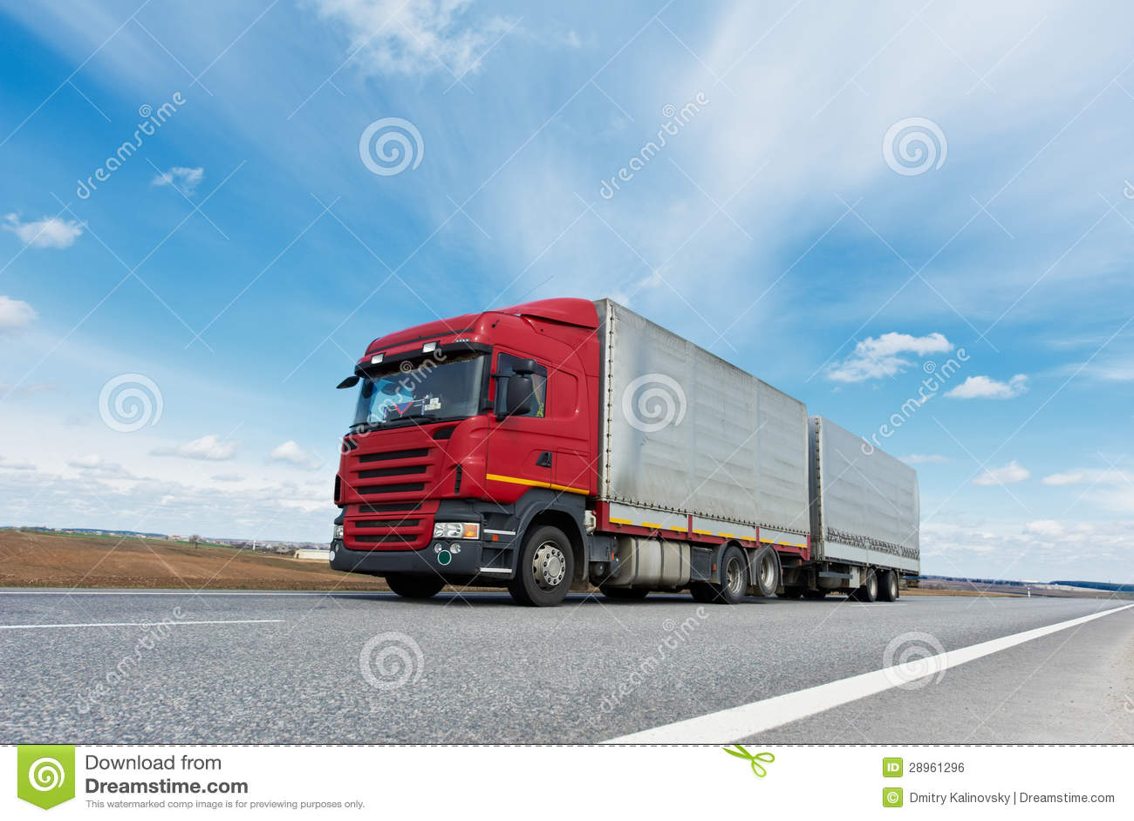 Czerwona ciężarówka z popielatą przyczepą nad niebieskim niebem