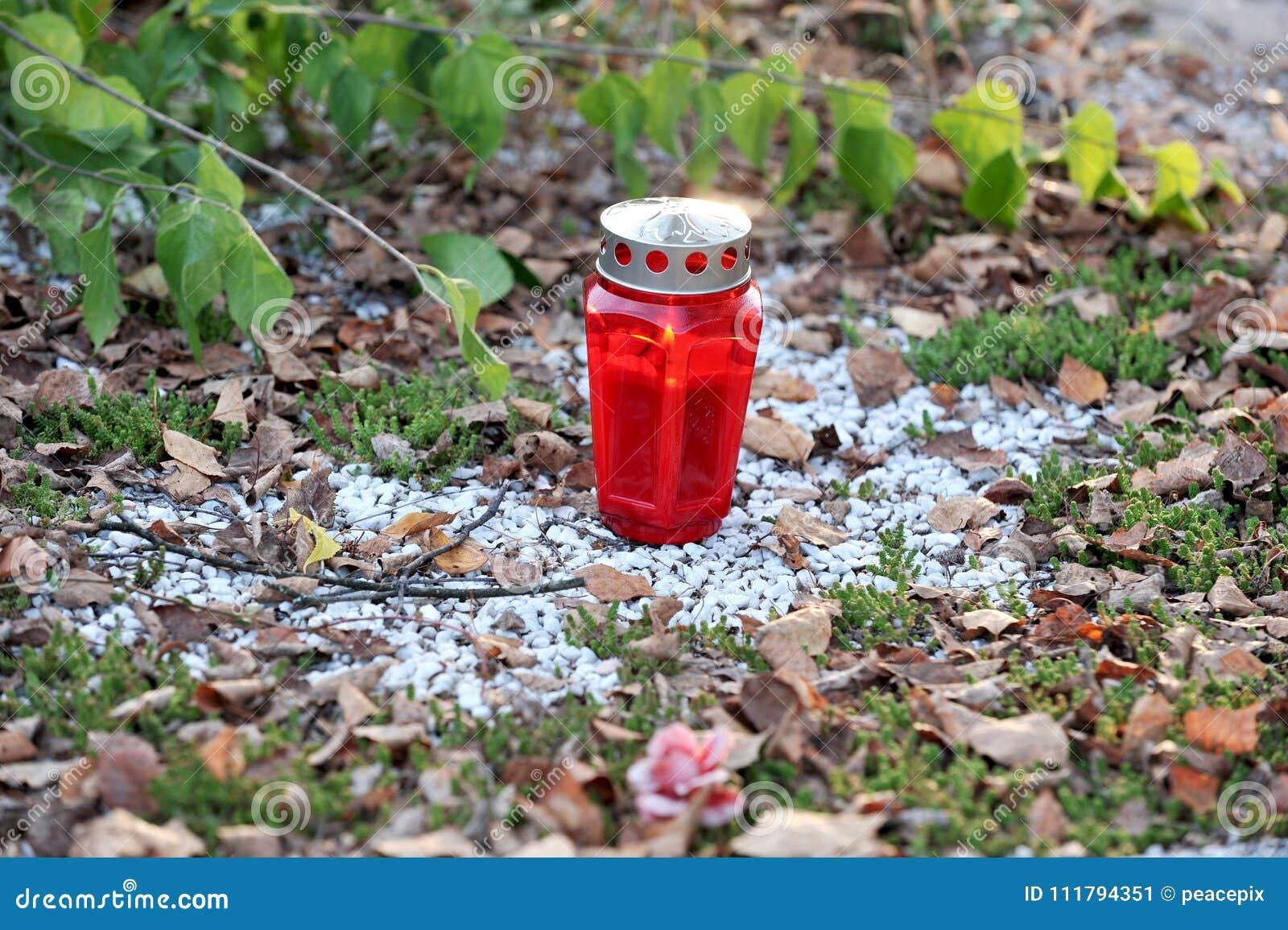 Czerwona cmentarz świeczka na białej kamienistej ziemi