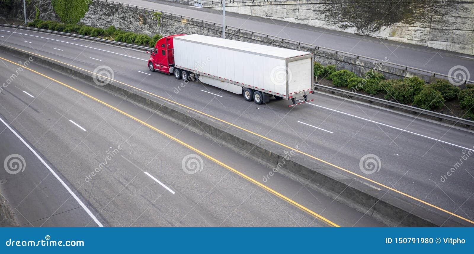 Czerwona duża takielunku dalekiego zasięgu semi ciężarówka z suchym samochodu dostawczego semi przyczepy bieg na dzielącej szerok