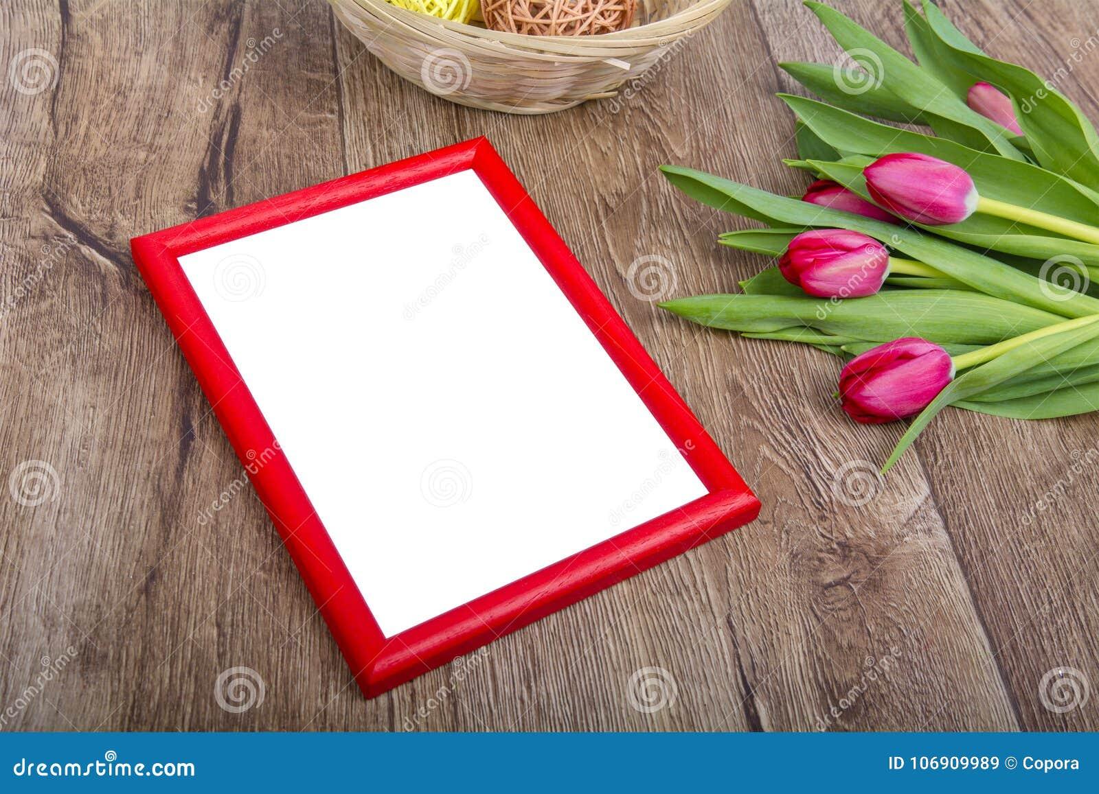 Czerwona fotografii rama, tulipany na stole i