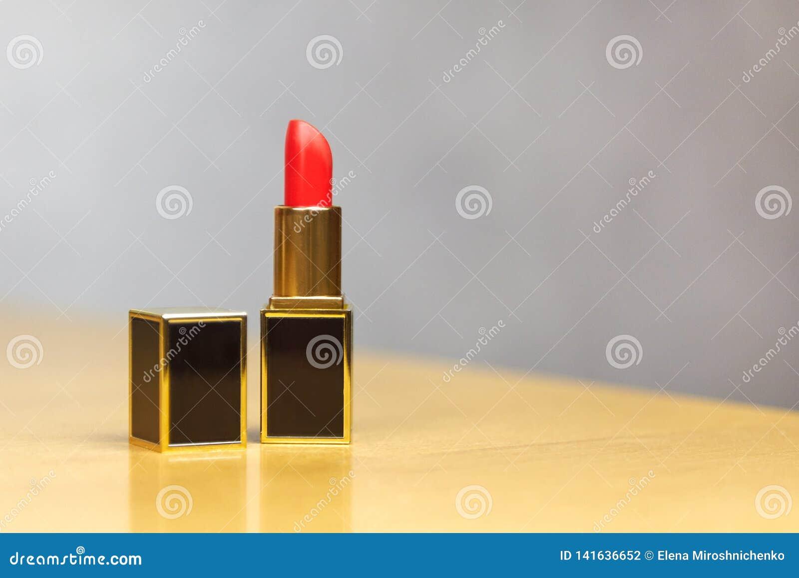 Czerwona pomadka z otwartą pokrywą, prostokątnym kształtem czerń i złoto luksusowa tubka, osiedlał na lekkim drewnianym stole Mod