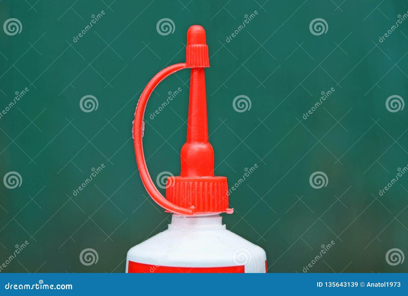 Czerwona tubka zamykał plastikowej tubki na zielonym tle