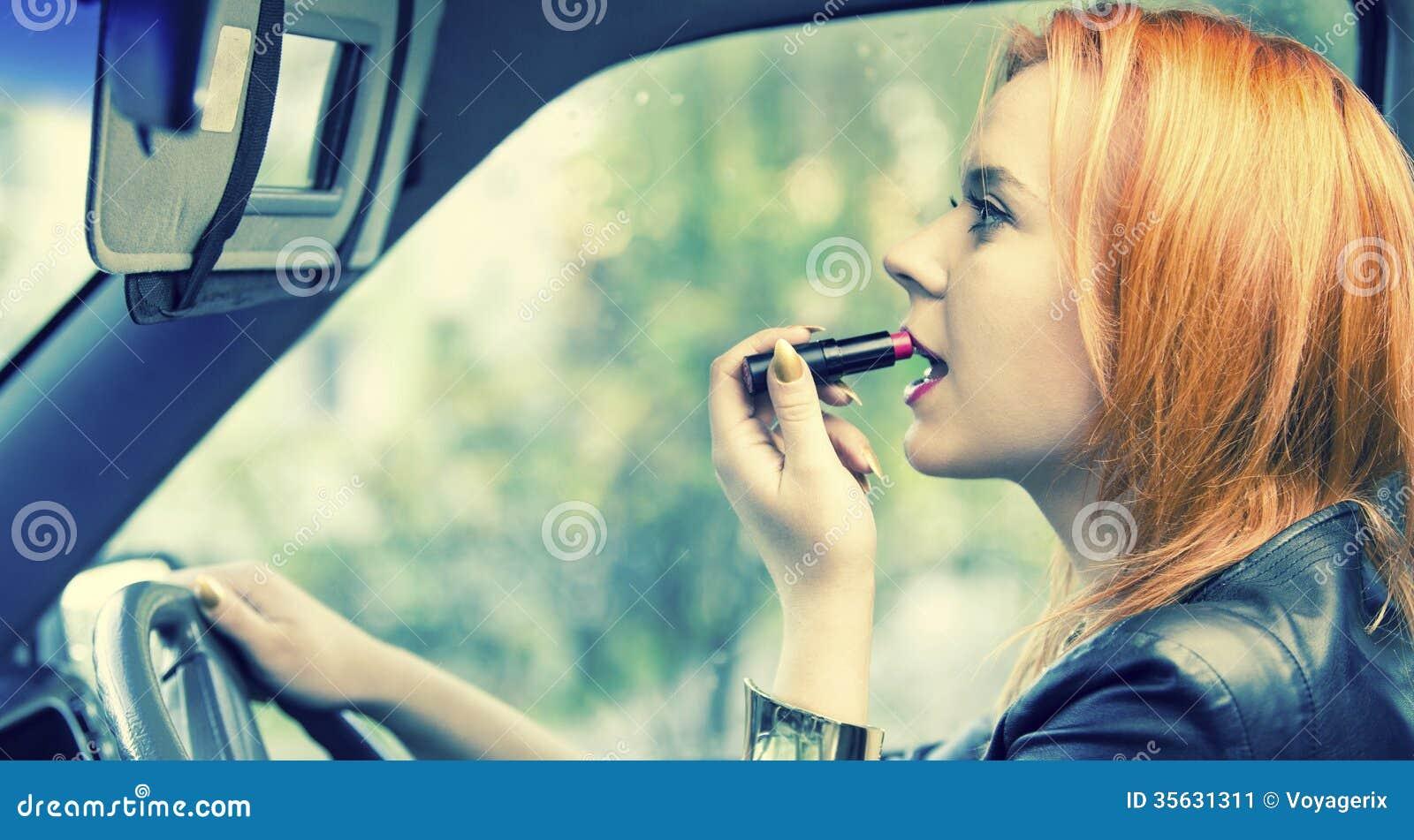 Czerwona z włosami kobieta stosuje pomadkę na wargach w samochodzie. Niebezpieczeństwo na drodze.