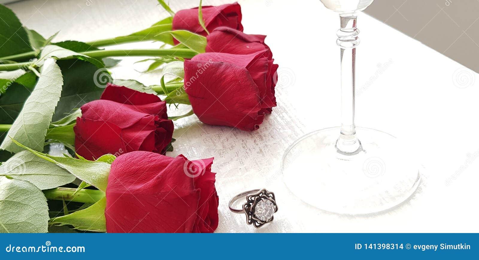 Czerwone róże kłaść na bielu stołu srebra pierścionku z dużym jasnym diamentem blisko