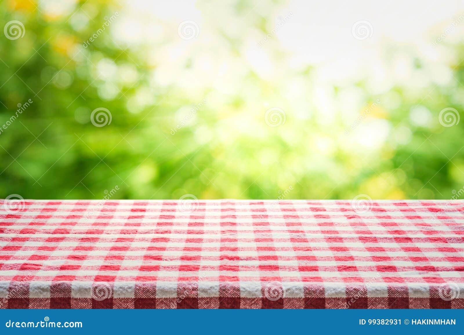 Czerwonej w kratkę tablecloth tekstury odgórny widok z abstrakt zieleni bokeh