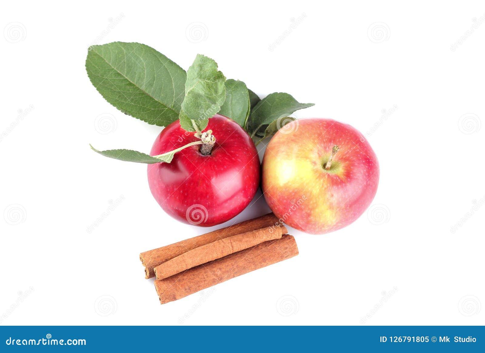 Czerwoni jabłka z liśćmi i cynamonowymi kijami na białym odosobnionym tle