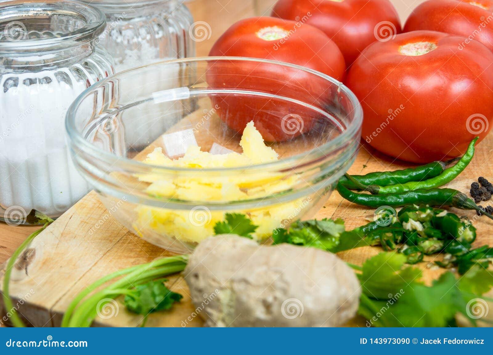 Czerwoni pomidory z pikantność i ziele na drewnianej desce w kuchni