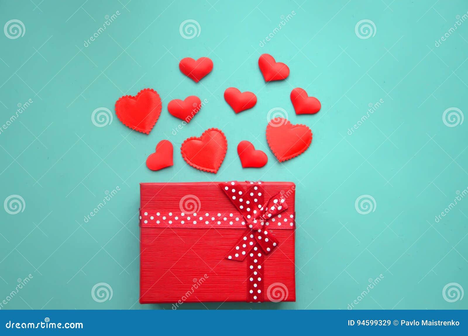 Czerwoni serca i prezenta pudełko na tle
