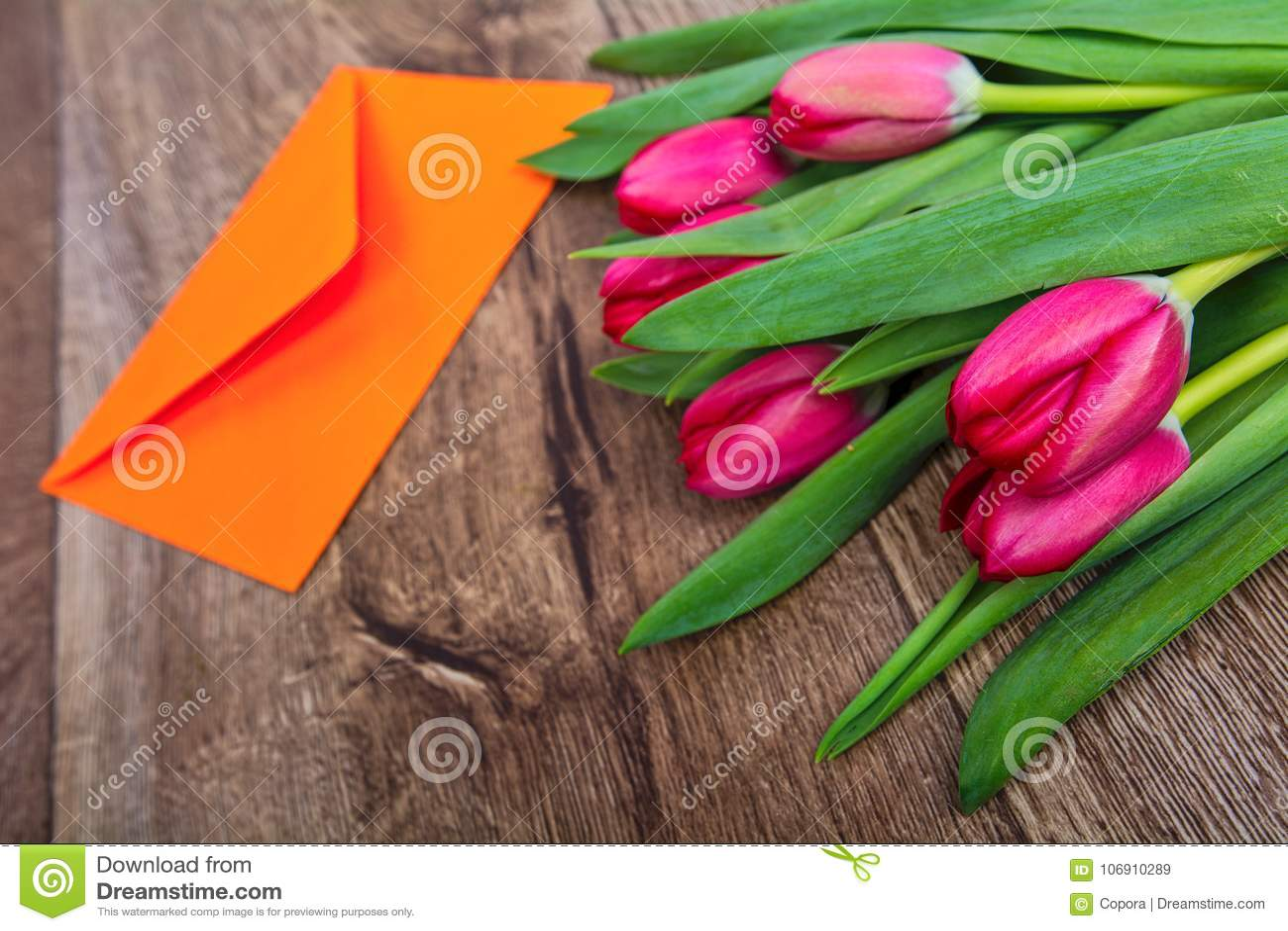 Czerwoni tulipany i koperta na drewnianym stole