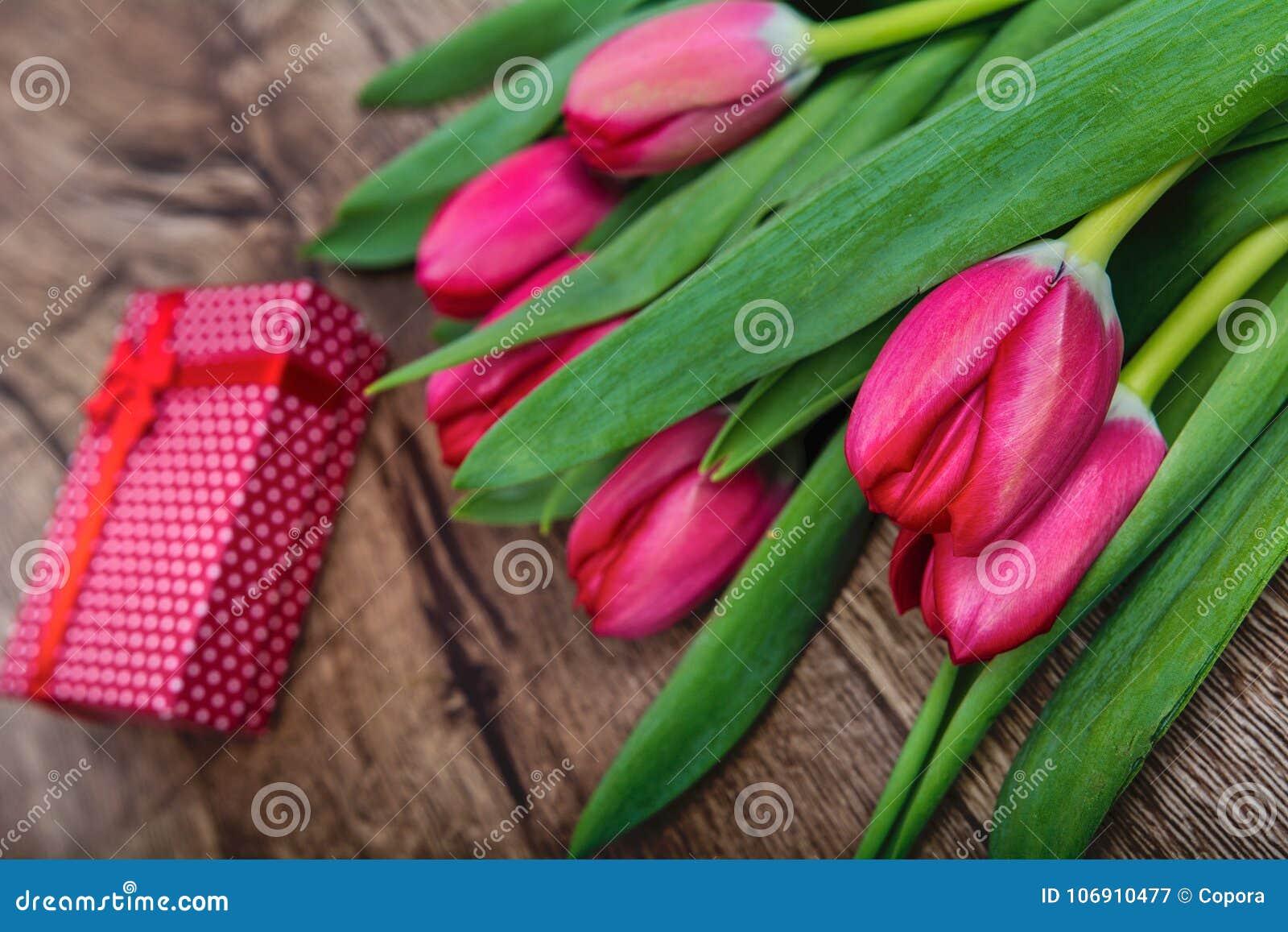 Czerwoni tulipany i prezent na drewnianym stole