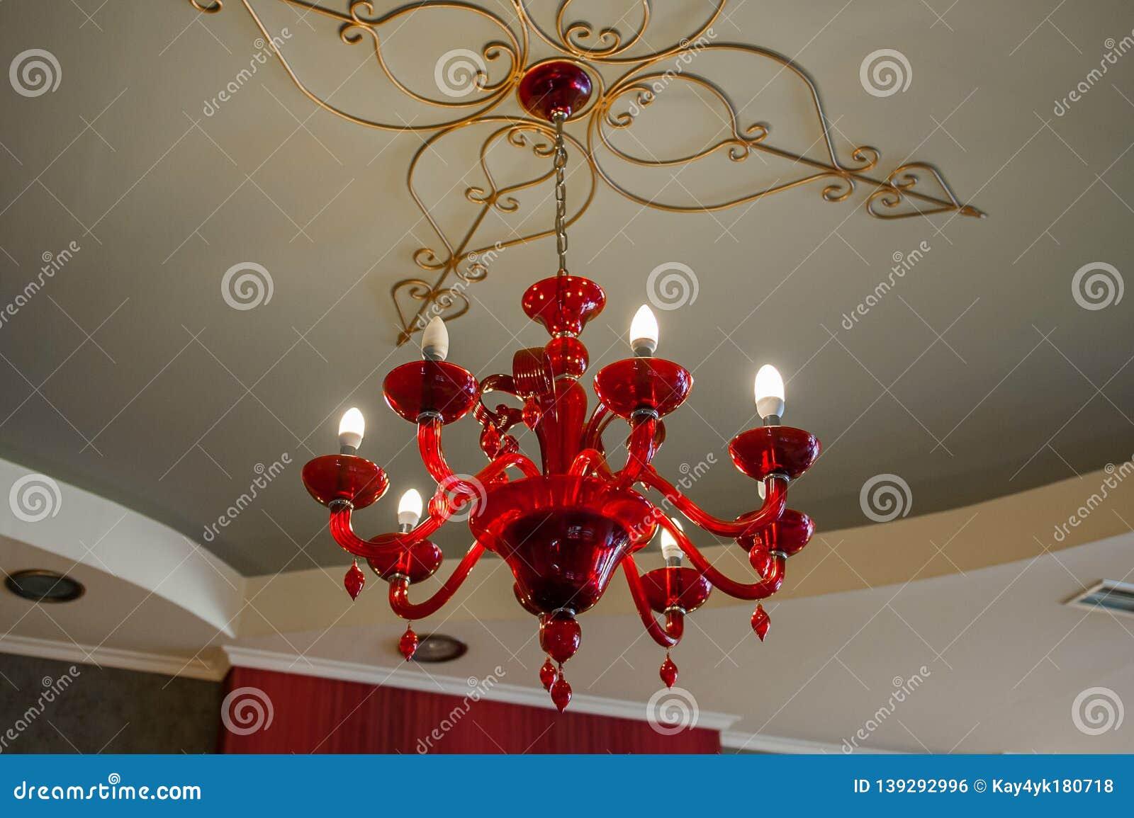 Czerwony świecznik na wzorzystym suficie w ciemnym pokoju, rozjarzone żarówki na nim