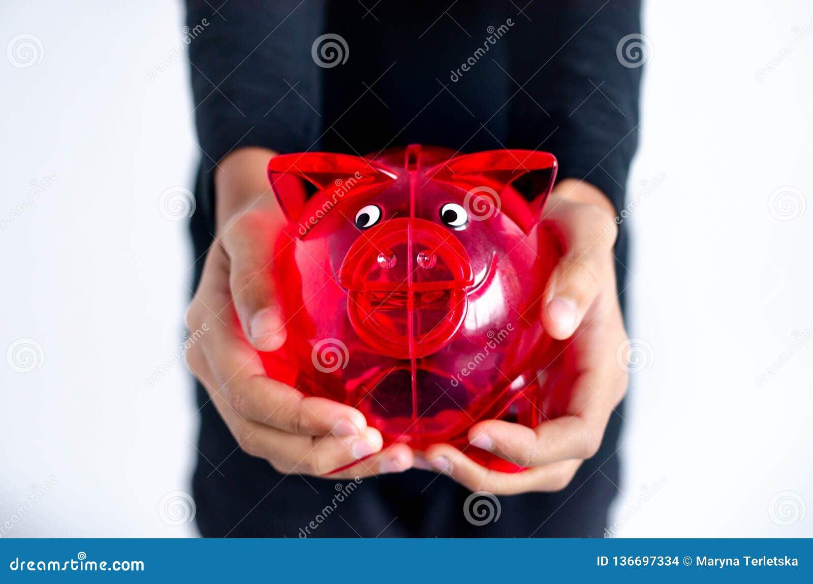 Czerwony świniowaty pieniądze pudełko w rękach ciemnoskóra dziewczyna