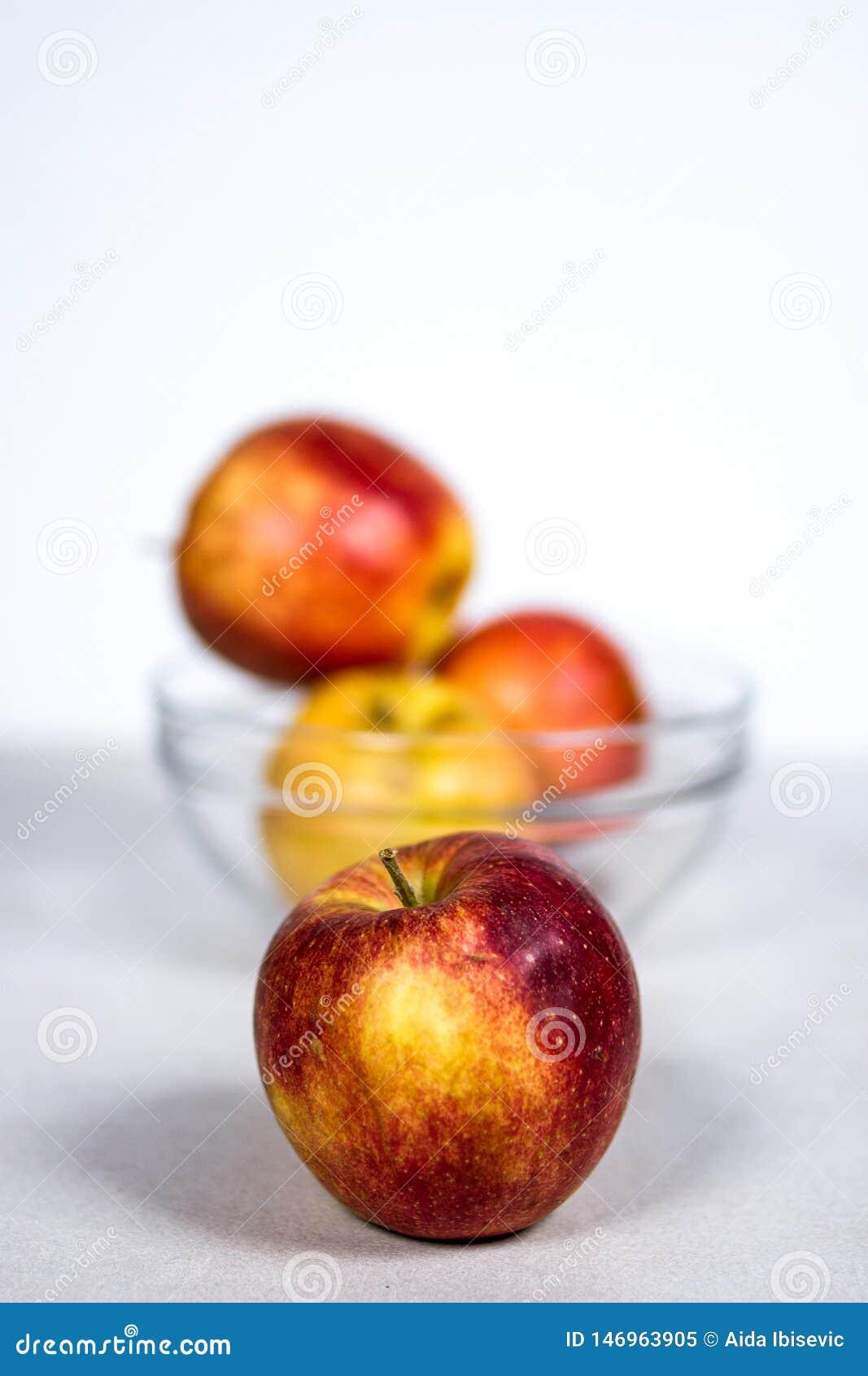 Czerwony Żółty Galowy Apple przed Szklanym Owocowym pucharem