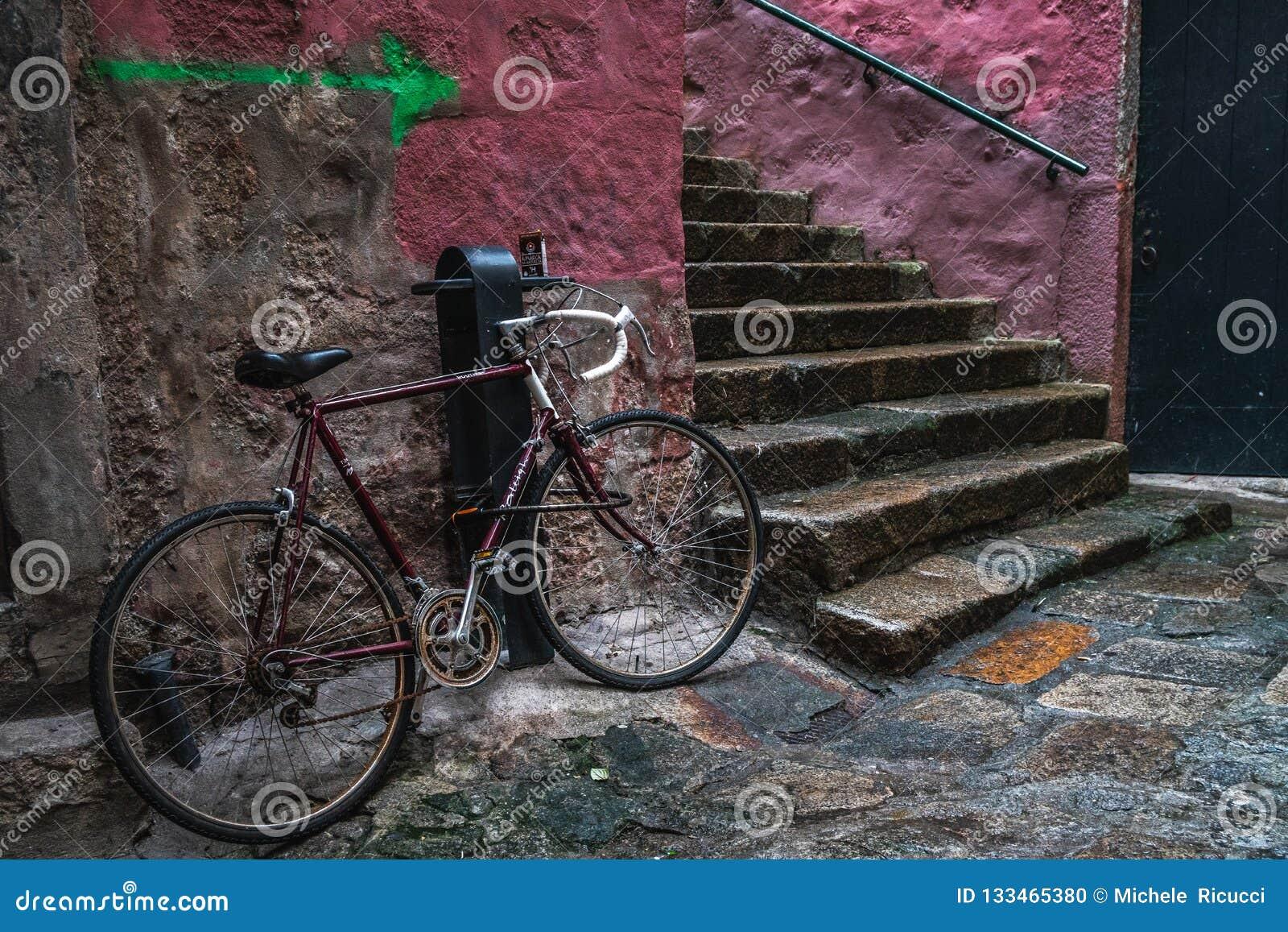 Czerwony bicykl w ulicie stary kamienny mały miasteczko