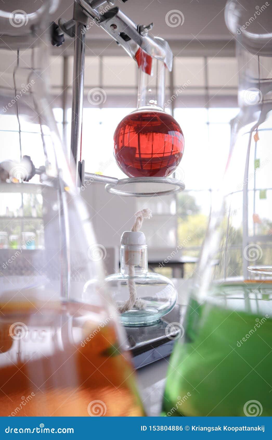 Czerwony ciecz w szklanej probierczej kolbie na stojaku Alcolhol lampowy miejsce z zamazanym pomarańcze i zieleni chemicznym labo