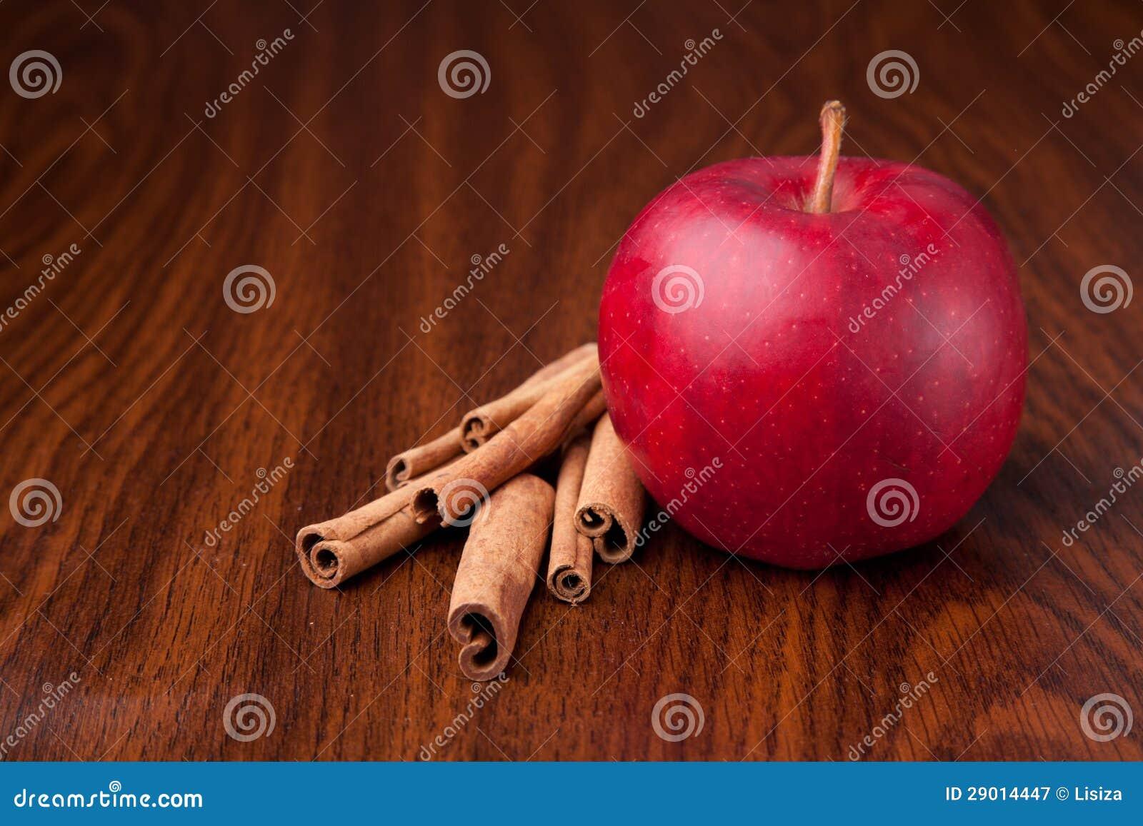 Czerwony jabłko na ciemnym drewnianym stole z kijami cynamon