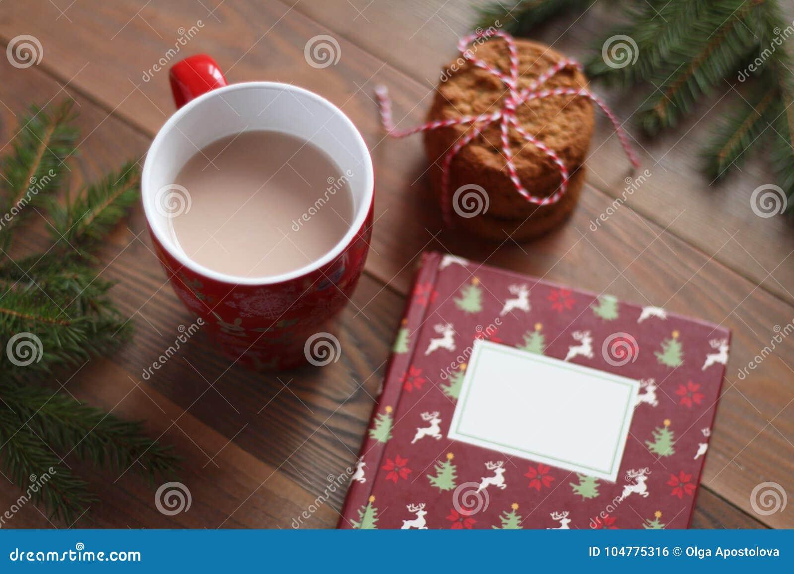 Czerwony kubek kakao, Bożenarodzeniowa książka i stos ciastka na drewnianym stole,