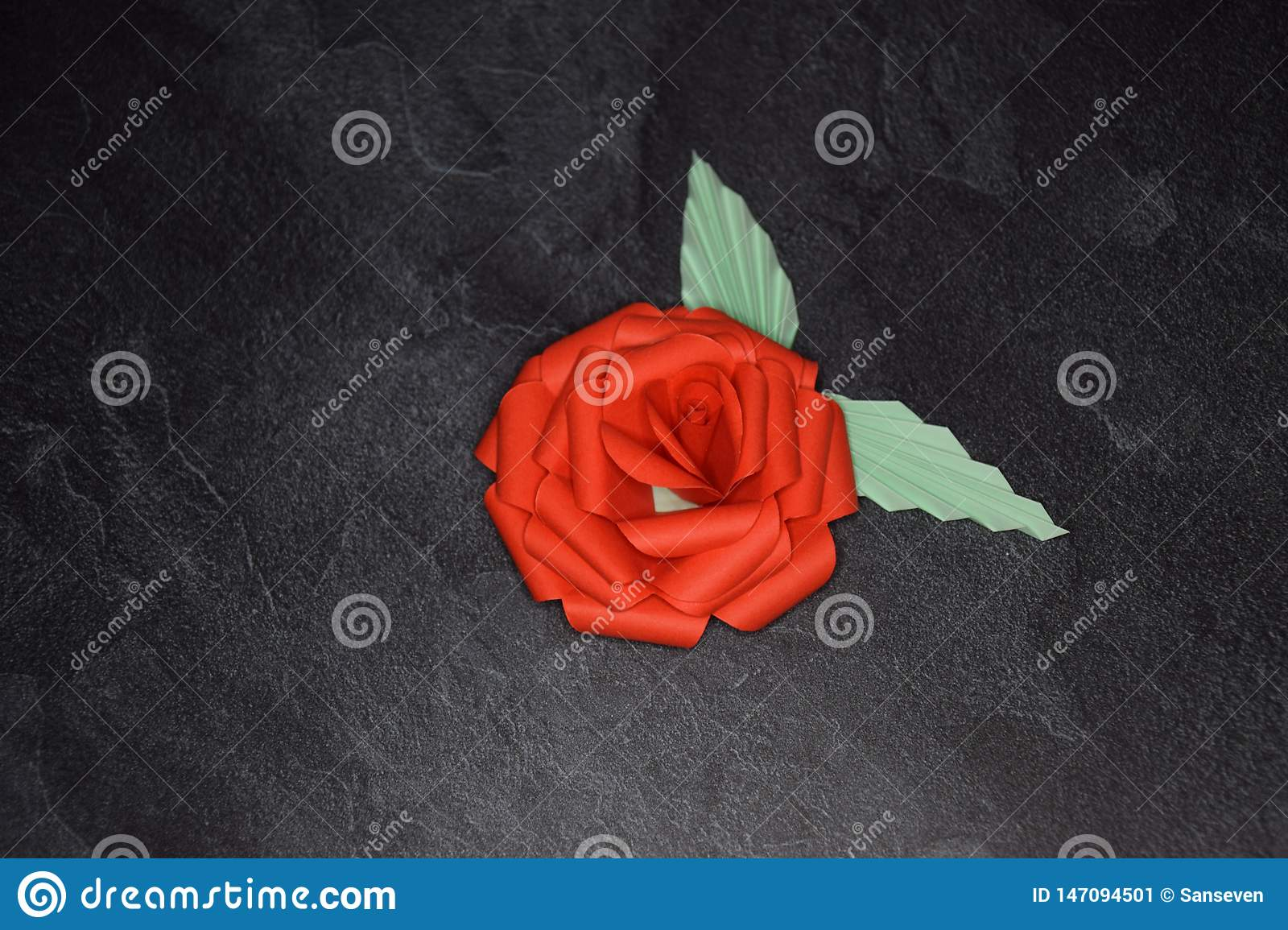 Czerwony Origami róży okwitnięcie - Papierowa sztuka na Textured tle