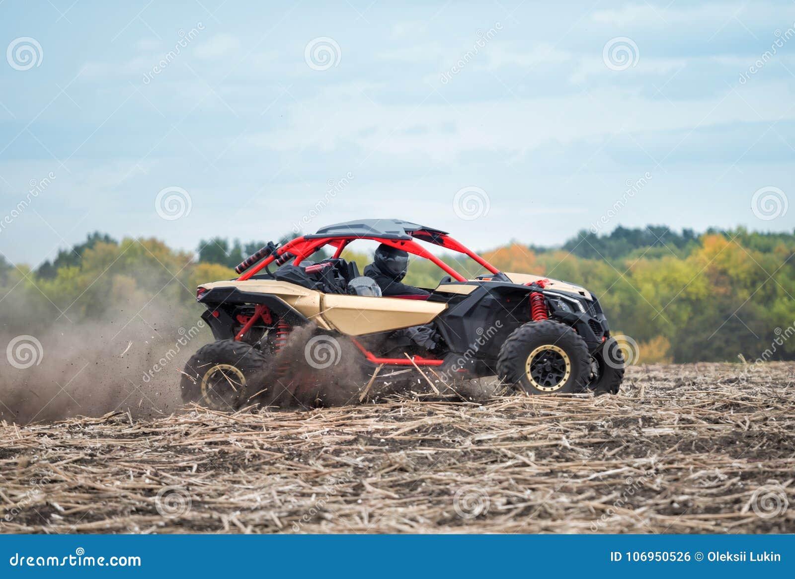 Czerwony powozik z dwa ludźmi w hełmach na zaoranym polu w pyle