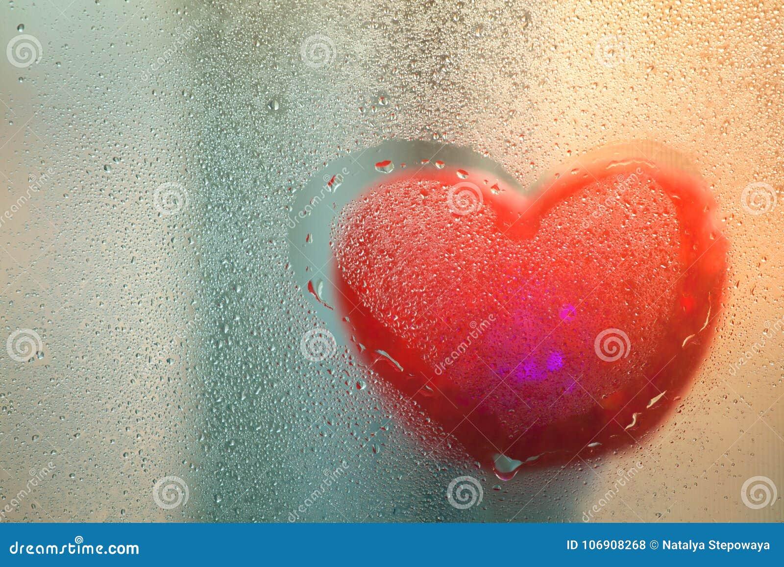 Czerwony serce na mokrym szkle po deszczu