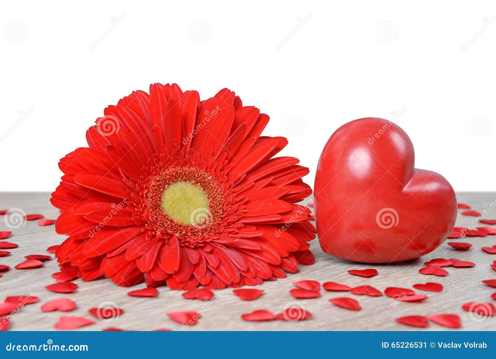 Czerwony serce z gerbera kwiatem na stole