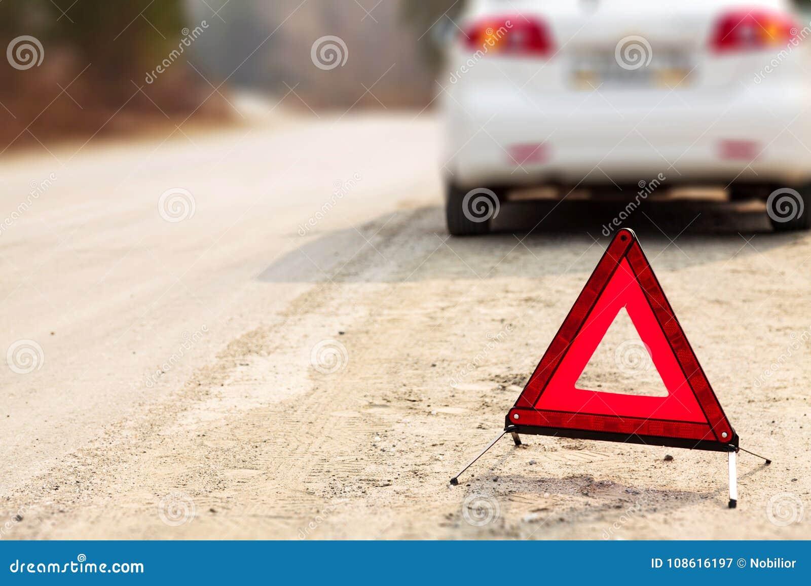 Czerwony trójboka znak, samochód na drodze i