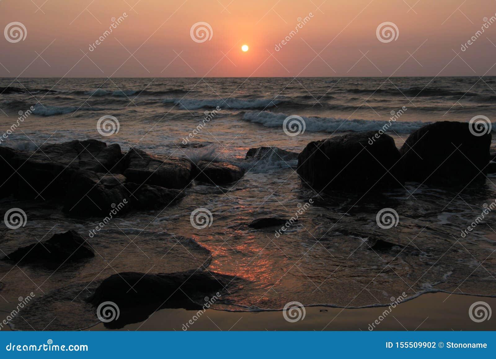 Czerwony zmierzch w koszcie z kamieniami ocean