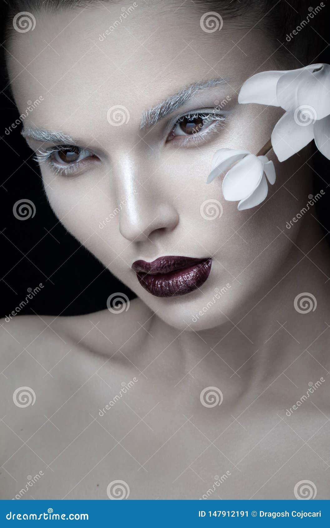 Czołowy widok piękno portreta artystyczny makeup, Burgundy wargi, twarz, blisko białego kwiatu, odizolowywającego na czarnym tle