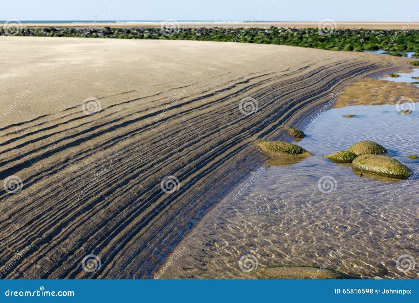 Czochry W piasku - wzór Robić na Northam plaży Otwartym przypływem Z otoczakami i Atlantyckim oceanem,