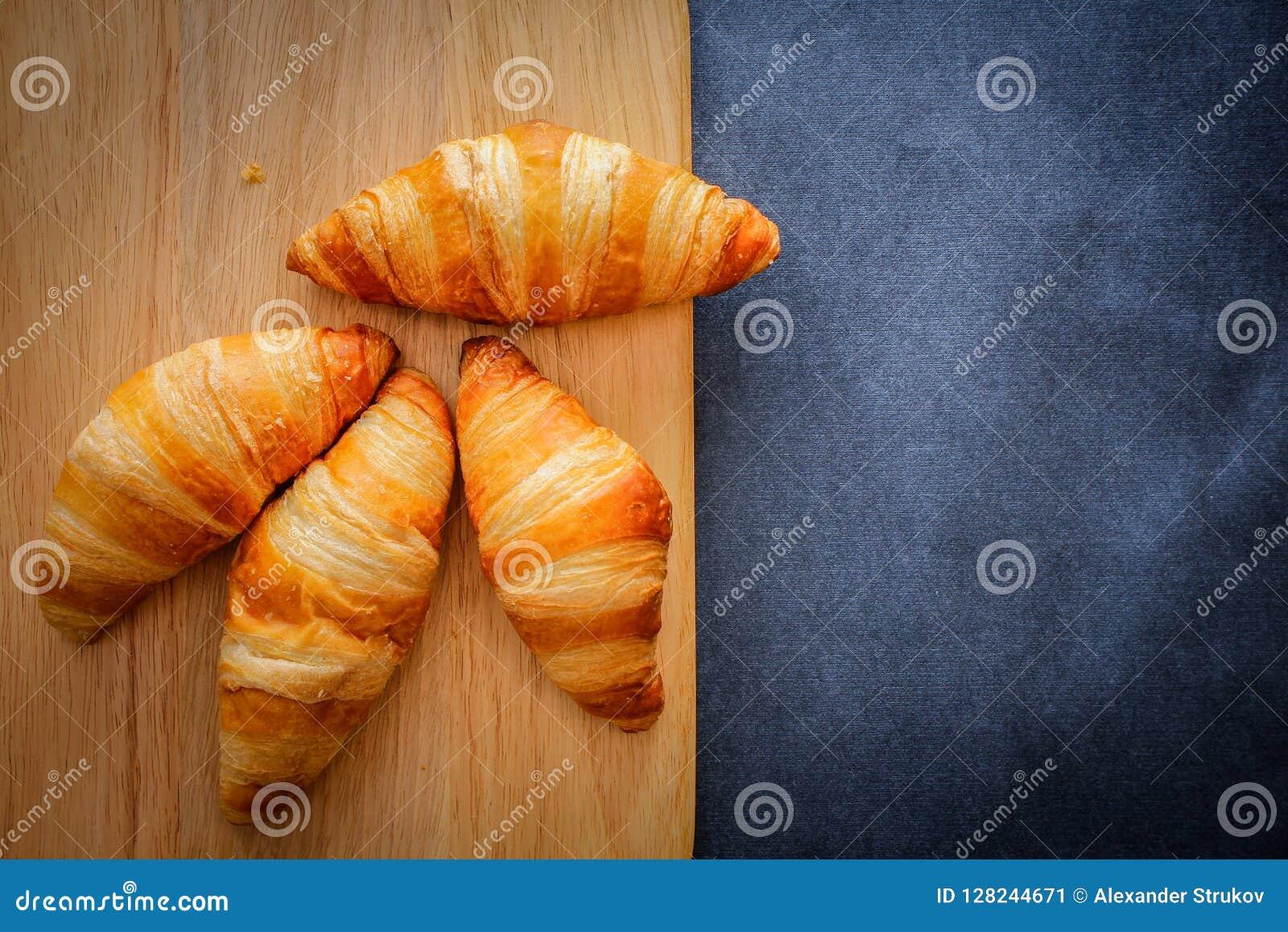 Cztery croissants na drewnianej lekkiej tnącej desce na ciemnym rzemiośle tapetują