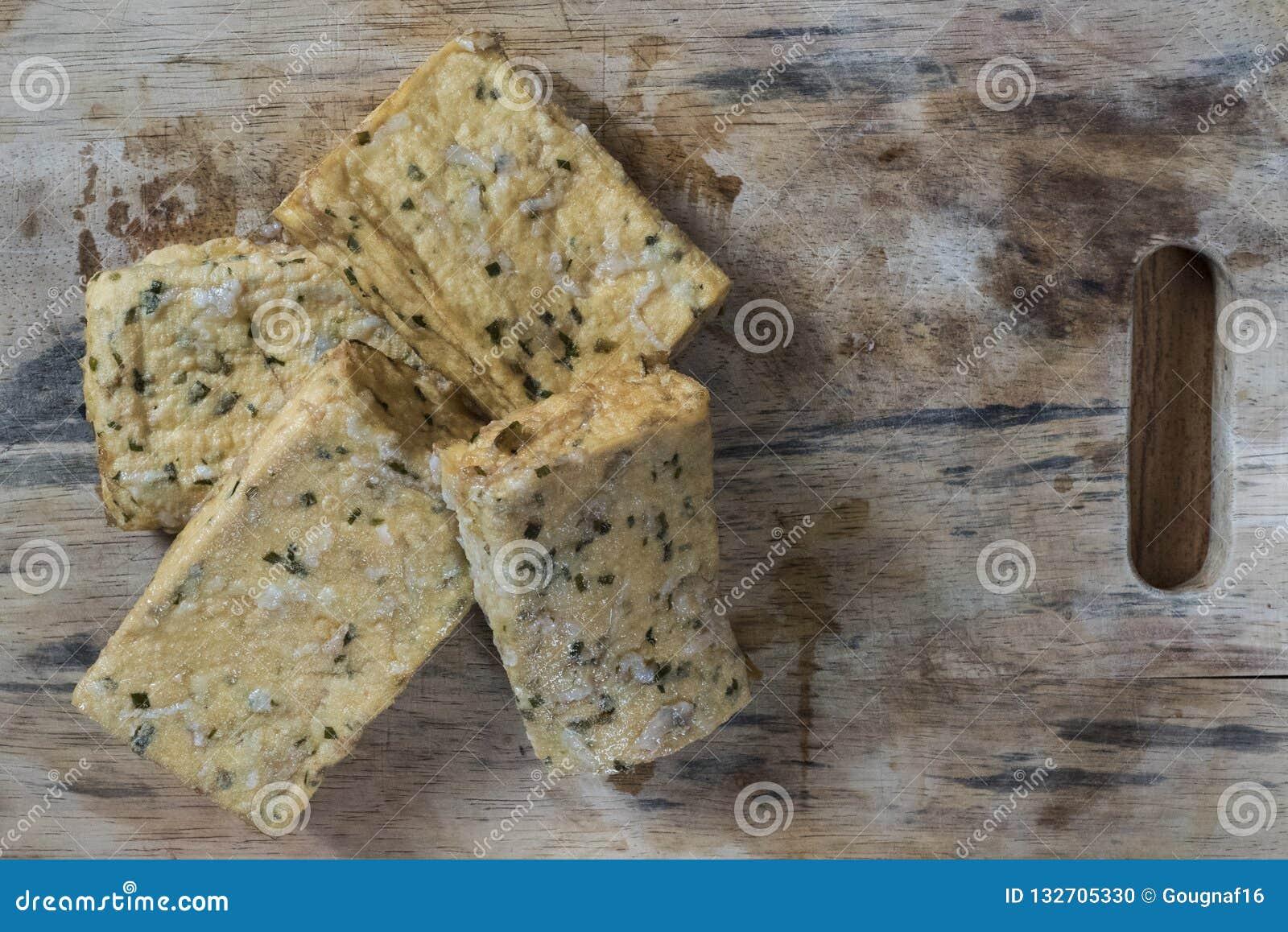Cztery kawałka tofu z ziele na drewnianej desce