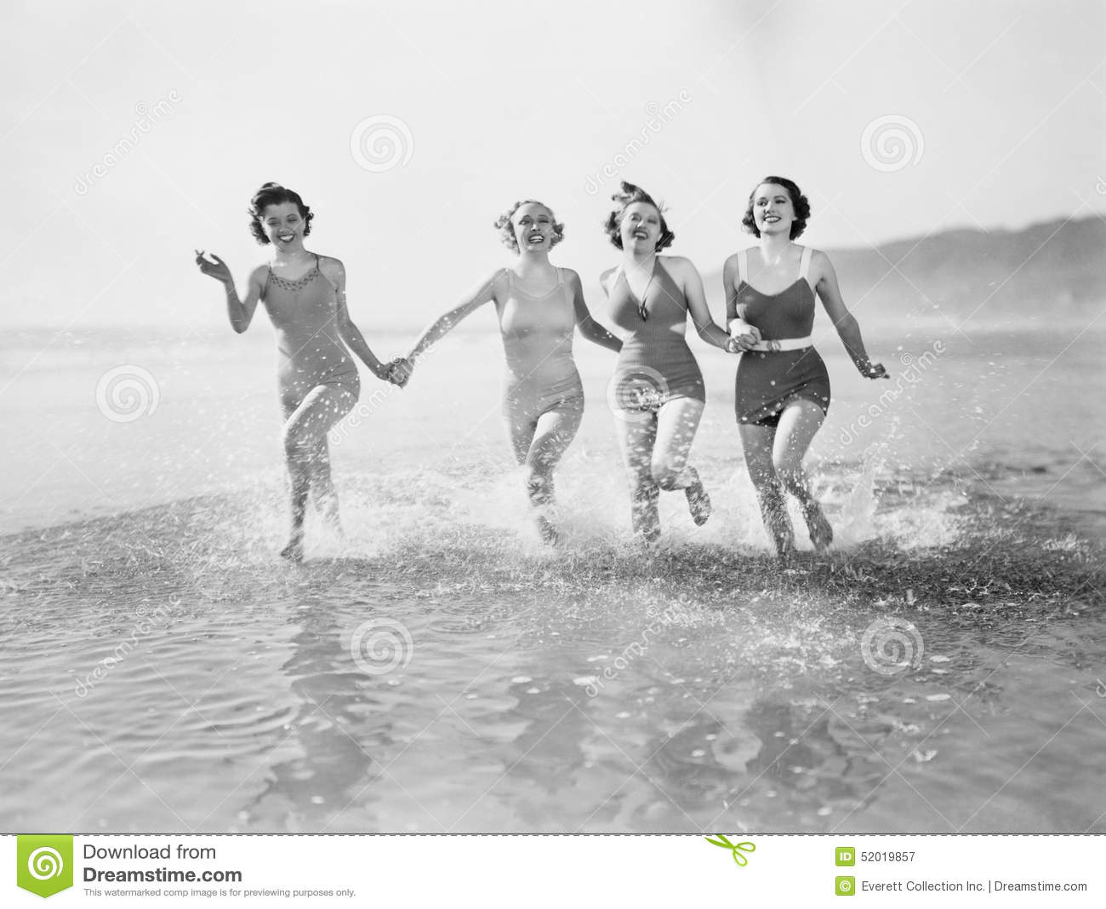Cztery kobiety biega w wodzie na plaży (Wszystkie persons przedstawiający no są długiego utrzymania i żadny nieruchomość istnieje