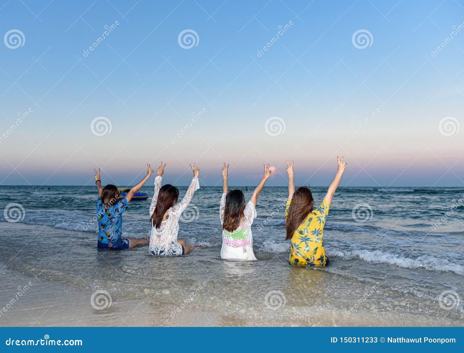 Cztery kobiety byli przyjaciółmi siedzącymi z powrotem i podnoszącymi ich ręki na plaży,