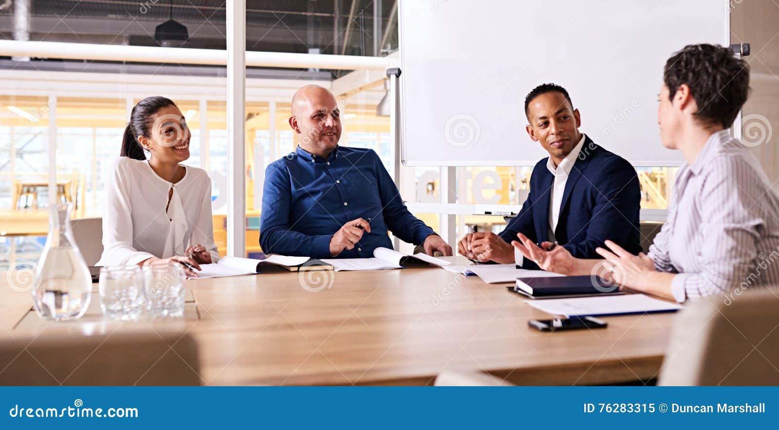 Cztery szczęśliwego ludzie biznesu ono uśmiecha się podczas ich tygodniowy spotykać wpólnie