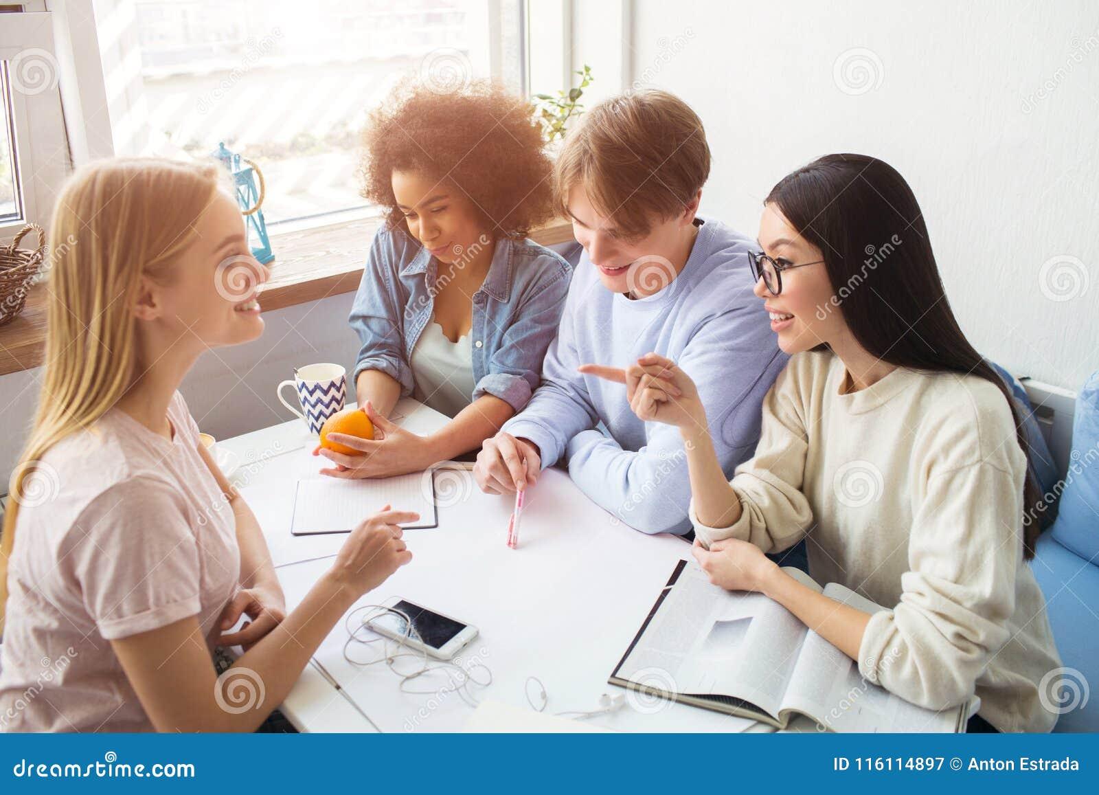 Cztery ucznia siedzą wpólnie przy stołem i mają rozmowę Afro amerykańska dziewczyna trzyma pomarańcze i
