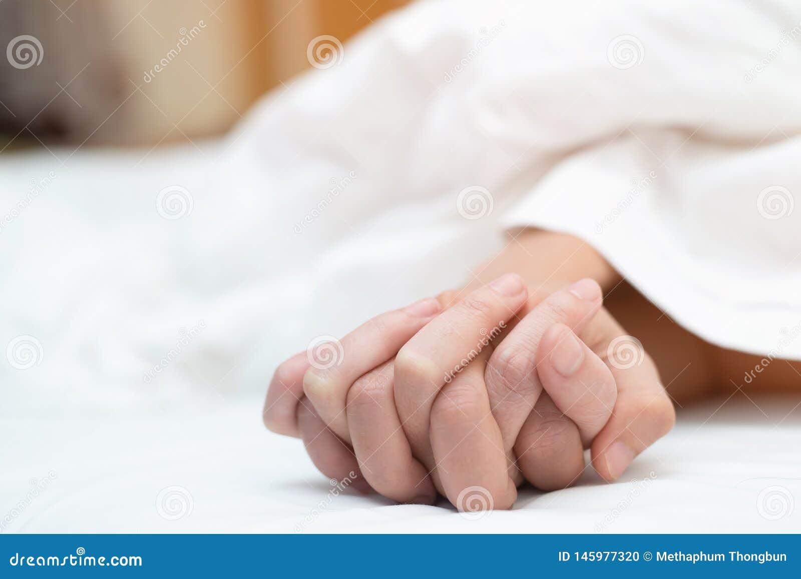 Czuć na rękach pasyjna para ma płeć dwa kochanek pary mienia ręki pod powszechnym bielem ciąć na arkusze na łóżku z żądzą i