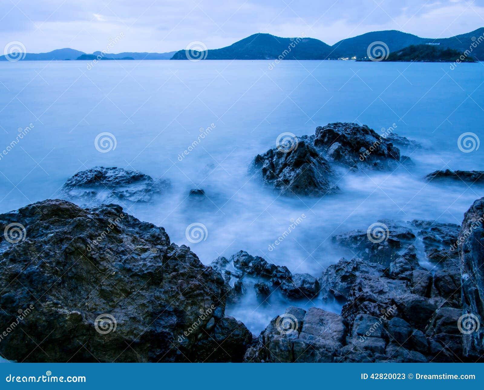 Dämmerung an den Küstenfelsen und -wellen
